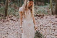 22 a boho lace wedding dress with an illusion V-neckline, cap sleeves and a sleek skirt