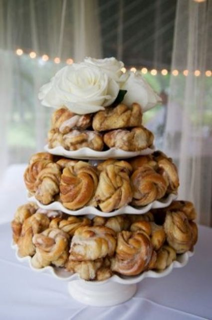 a cinnamon bun cake topped with white roses is ideal for a fall or winter bridal shower