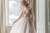 22 blush wedding dress with long tulle sleeves, a lace applique bodice and a layered skirt