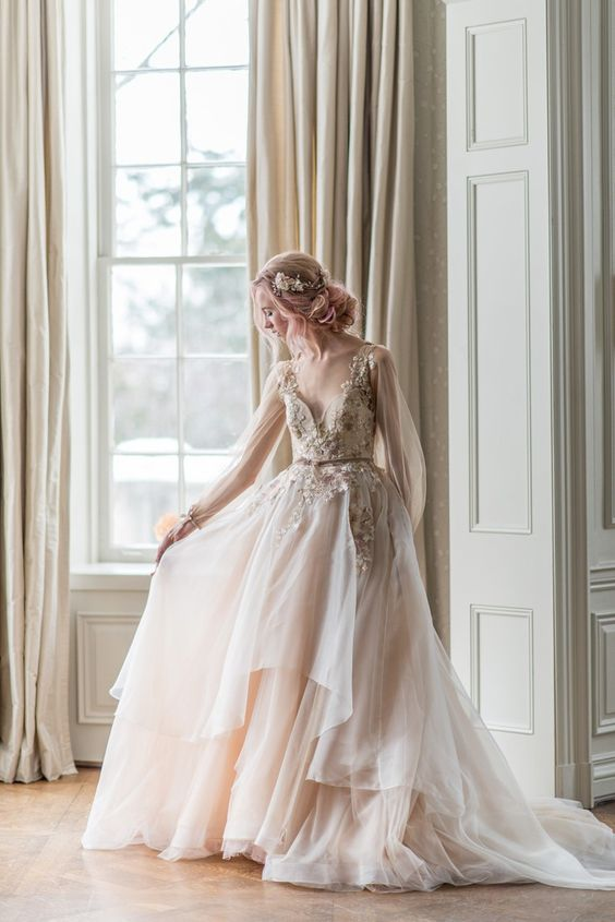 blush wedding dress with long tulle sleeves, a lace applique bodice and a layered skirt