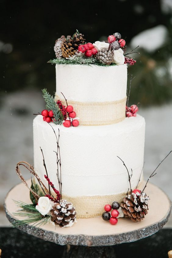 a chic wedding cake with berries, pinecones, evergreens and burlap ribbon