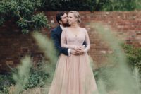 a dusty pink wedding dress with an embroidered sparkling bodice, long sleeves and a layered skirt