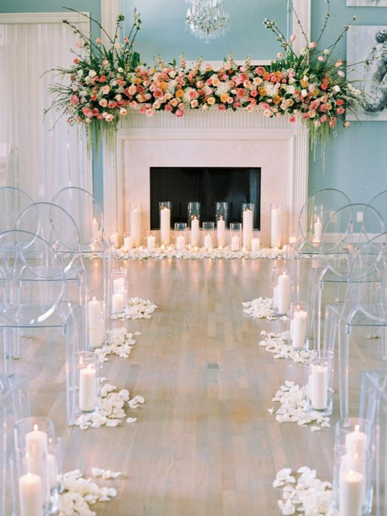 a faux fireplace lushly decorated with various blooms, greenery and lined up with candles looks very chic
