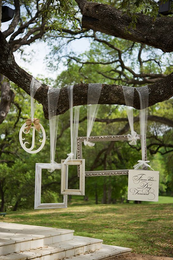 a fun photo booth with various frames hanging from the tree will make the pics cuter