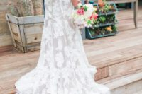 23 a lace wedding dress with no sleeves, an open back and a small train and a bridal sash
