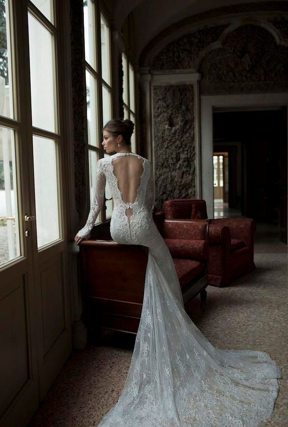 a lace wedding dress with long sleeves, a train and whimsy cutout back