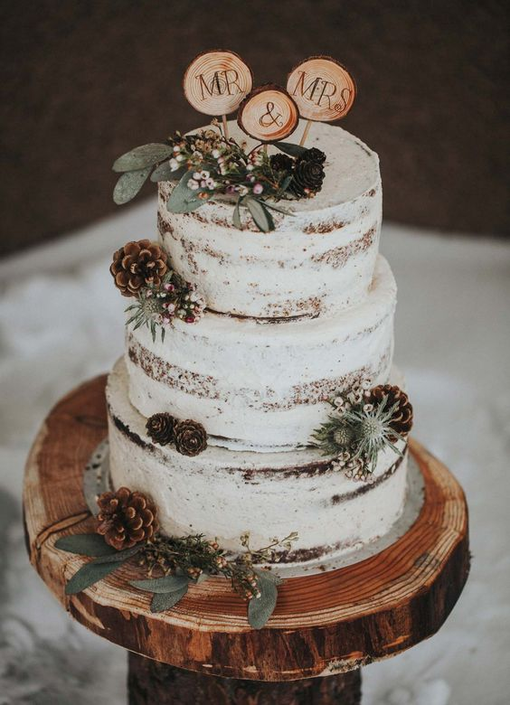 a semi-naked wedding cake with leaves, blooms and pinecones and wood slice toppers