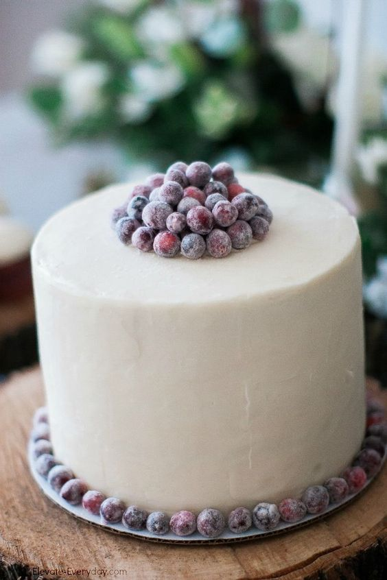 a white frosted cake with sugared berries is ideal for a winter bridal brunch