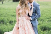 25 a pink sleeveless wedding dress with a plunging neckline and pearl floral embroidery all over the gown