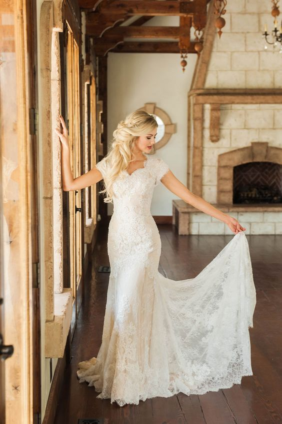 a sheath lace wedding dress with short sleeves and a train