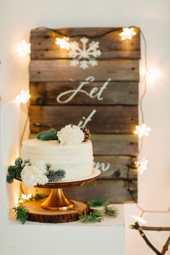 a white frosted wedding cake topped with blooms, pinecones and fir branches