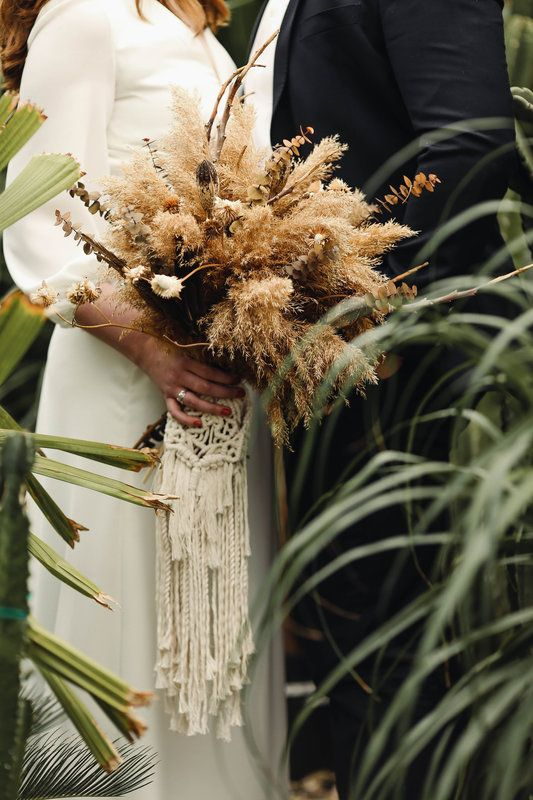 earthy boho wedding bouquet is accessorized with a macrame wrap with fringe