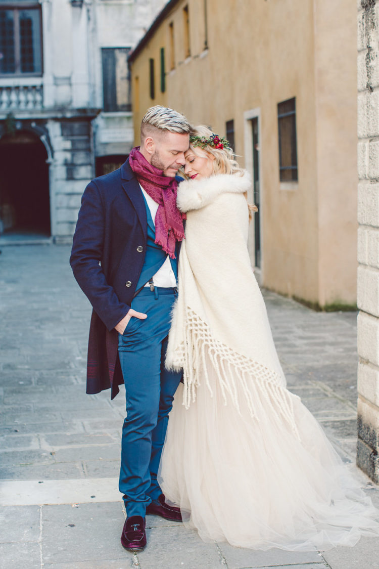 the groom wearing a bold blue suit, a navy coat, burgundy moccasins and a burgundy scarf