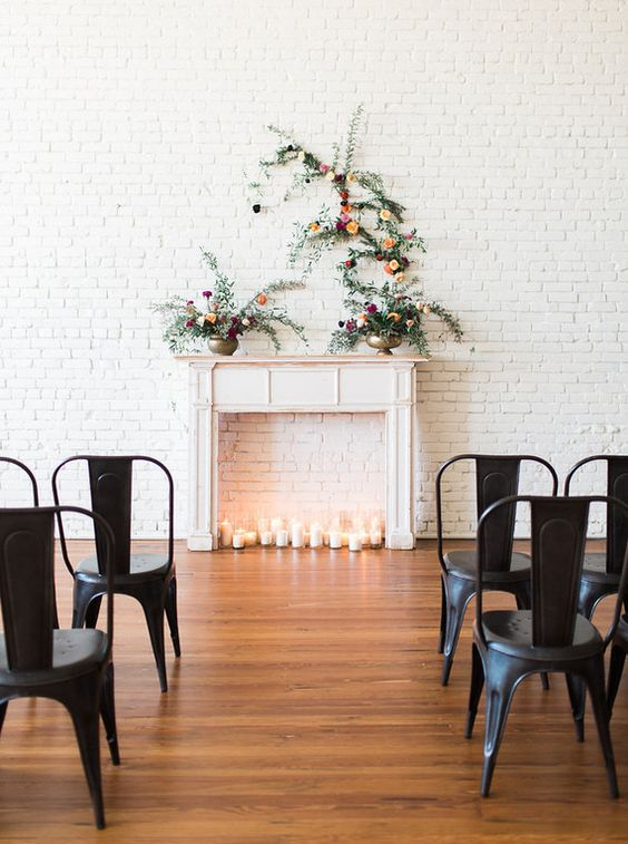 a faux fireplace in front of a whitewashed brick wall, candles and floral arrangements on the mantel for a beautiful look