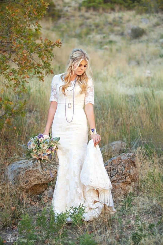 a sheath scoop neckline lace applique wedding dress with short sleeves and a train can be accessorized with layered necklaces