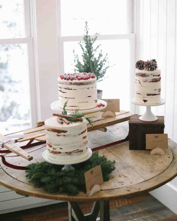 an assortment of semi-naked cakes topped with cinnamon bark, berries and pinecones