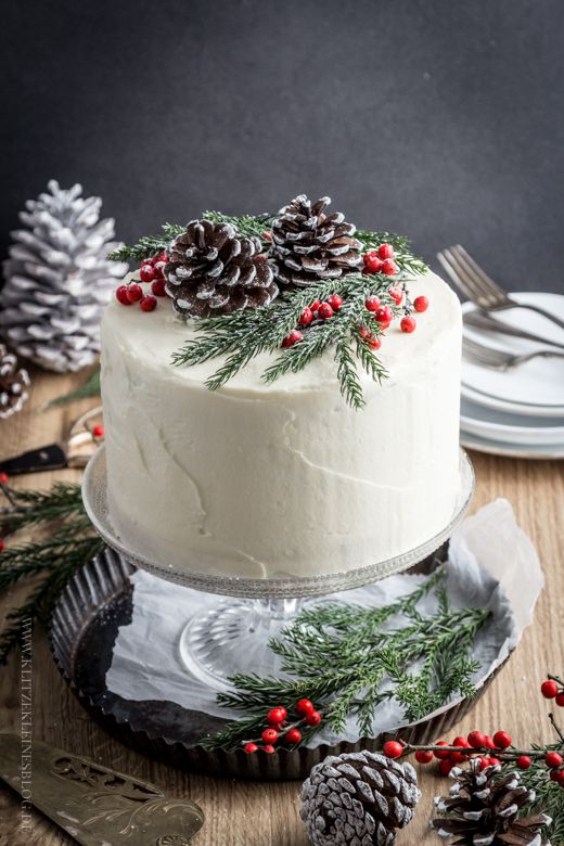 a winter frosted wedding cake topped with berries, evergreens and snowy pinecones