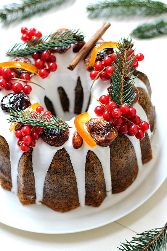 poppy seed bundt cake with white chocolate drip, cranberries, evergrenes, cinnamon and candied fruit