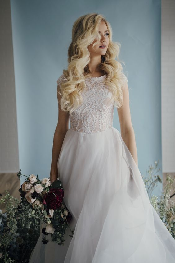 A-line wedding dress with a textural lace bodice with cap sleeves and a layered tulle skirt
