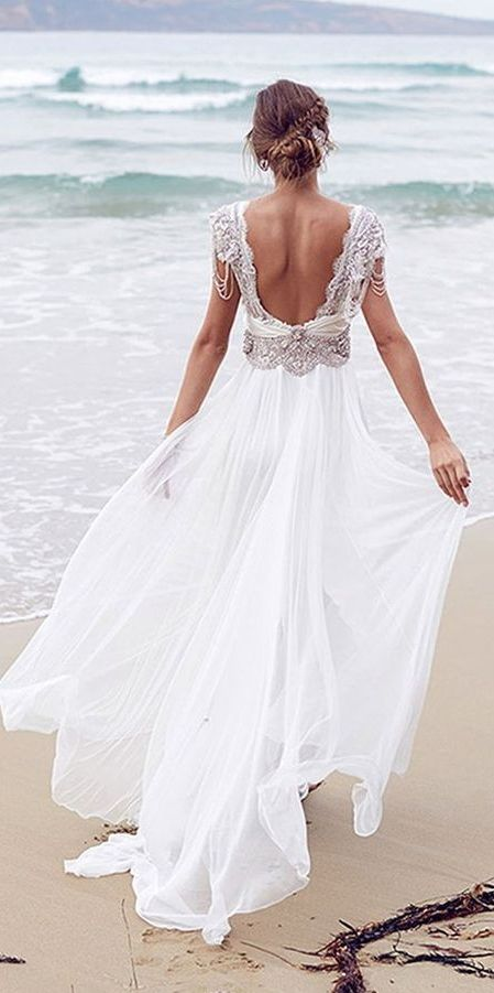 a beaded wedding dress with cap sleeves, an ethereal skirt and a cutout back