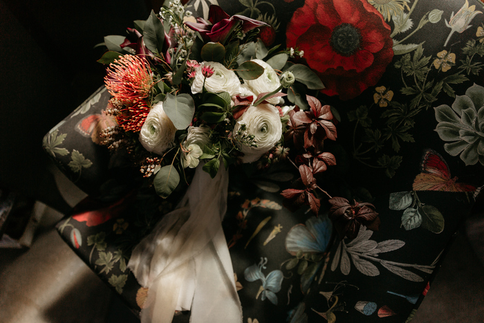The wedding bouquet was done in red and white, with airy ribbons