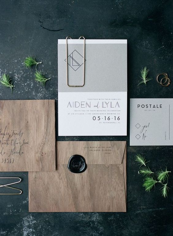 an industrial stationery set with wood print envelopes and a grey and white invite