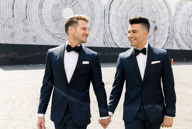 The grooms were wearing navy tuxedos with black lapels and matching hairstyles