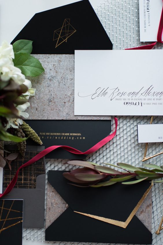 a modern industrial wedding invitation suite with black and gold geometric touches and stone print