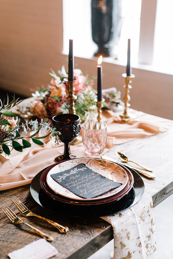 The tablescape was styled with a blush table runner, black, maroon and blush plates and touches of gold