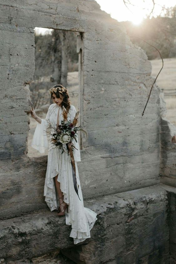 a boho lace wedding dress with a plunging neckline, bell sleeves, a high low skirt with a train for a boho look