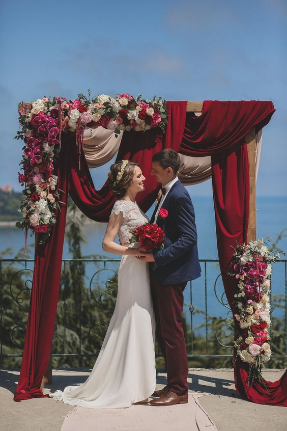 a gorgeous wedding arch with burgundy draperies, pink, fuchsia and red blooms