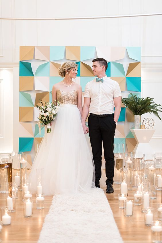 a modern paper geometric backdrop in gold and turquoise and lots of candles around