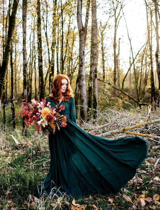 flowy emerald wedding dress for a fall bride and a contrasting bouquet