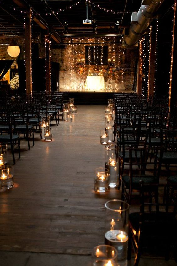 string lights hanging vertically and floating candles in jars make the industrial space look softer