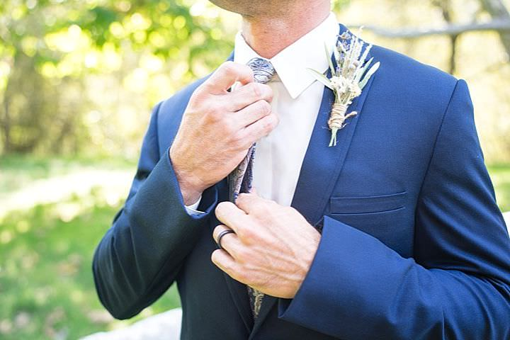 The groom was wearing a navy suit, a printed tie and a herb boutonniere