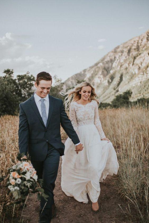 a boho lace wedding dress with a lace long sleeve bodice and a flowy skirt for a boho bride