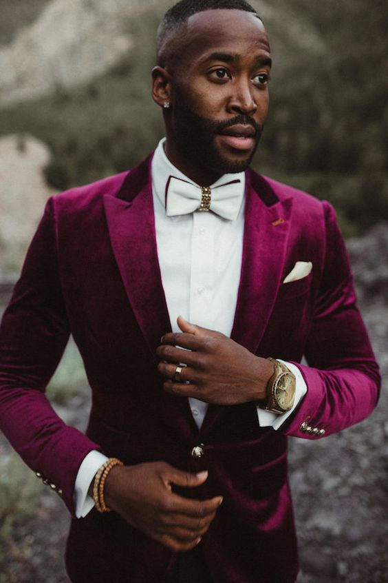 a glam groom in a plum-colored velvet tuxedo, a white shirt and an embellished white bow tie