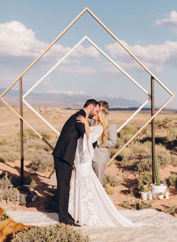 a modern geometric backdrop with cacti and a desert landscape behind it