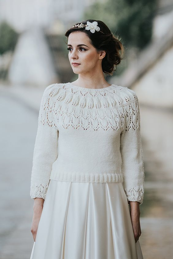 a white patterned cropped sweater with cropped sleeves and a pleated satin skirt