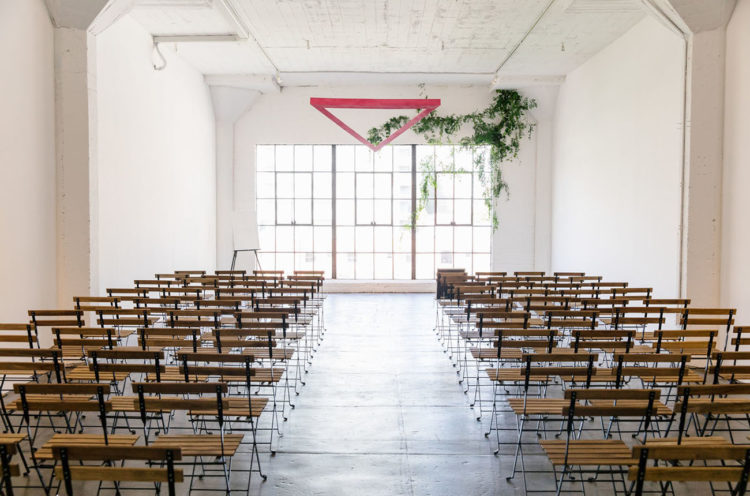 The ceremony space was a white one with a greenery and a pink triangle altar
