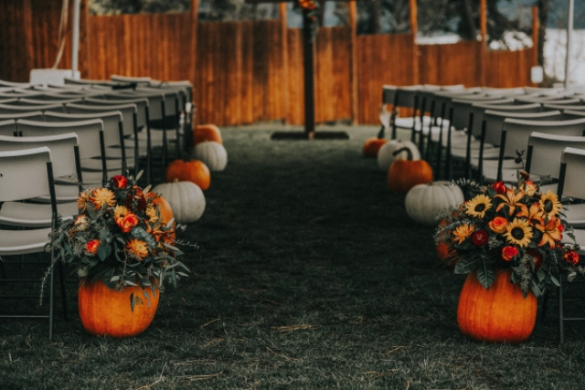 The wedding aisle was lined up with large pumpkins in orange and white