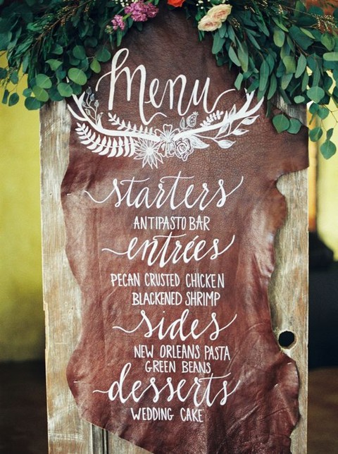 a brown leather wedding menu with white calligraphy is a chic badass idea to rock
