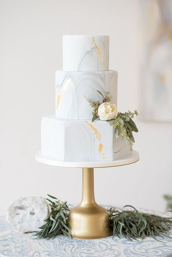 a marbleized wedding cake with light grey and gold leaf and a bloom
