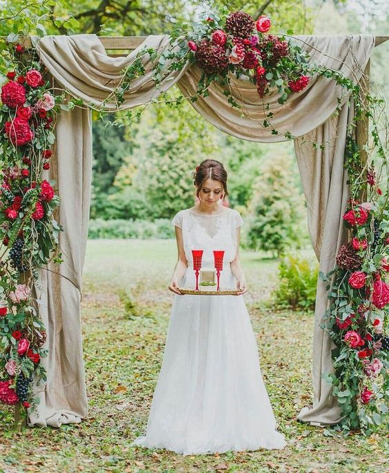a romantic red and burgundy floral wedding arch with grapes, greenery and neutral fabric