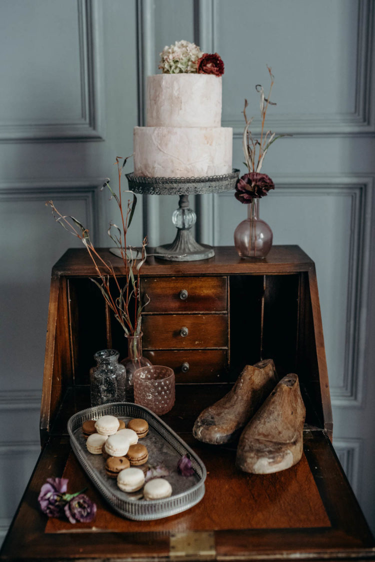 A vintage bureau was used as a dessert table for macarons and a raw plaster wedding cake with blooms