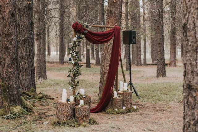 The groom made the altar by himself, with a fresh greenery garland and draped burgundy fabric
