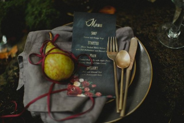 You can see grey napkins, plates, chargers and black menus with marsala florals