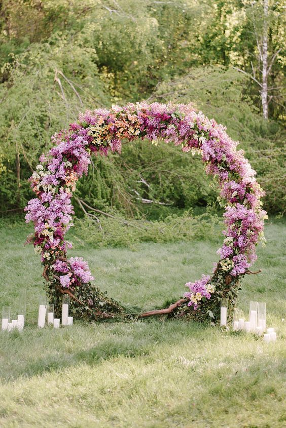 a bold circle floral arch in the shades of pink and lilac and some candles around