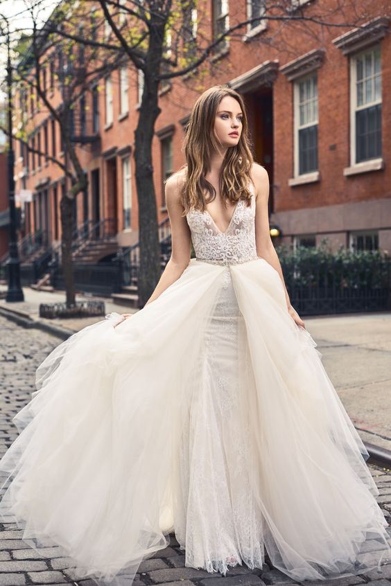 a lace sheath wedding dress with an overskirt, a deep V-neckline and wide straps