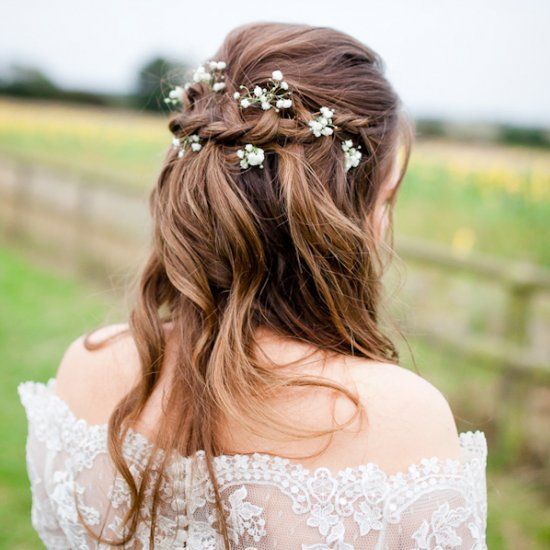 a messy braided half updo with waves and baby's breath for a boho, rustic or woodland bride